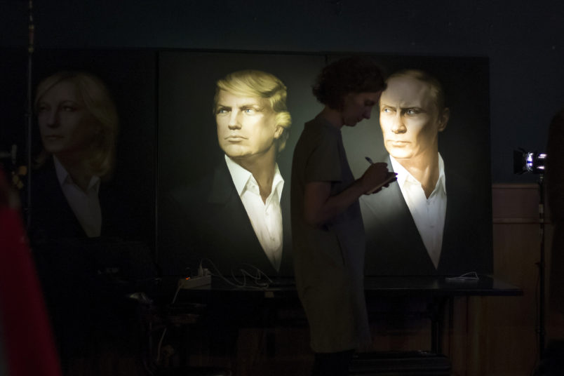 A journalist  writes a material as she watches a live telecast of the U.S. presidential election standing at portraits of Hillary Clinton, Donald Trump and Vladimir Putin in the Union Jack pub in Moscow, Russia, Wednesday, Nov. 9, 2016. Russia's lower house of parliament is applauding the election of Donald Trump as U.S. president. (AP Photo/Alexander Zemlianichenko)