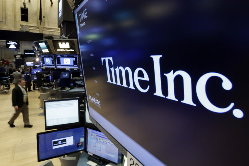 The Time Inc. logo appears above a trading post on the floor of the New York Stock Exchange, Thursday, June 15, 2017. Magazine publisher Time Inc. says it's cutting 300 jobs as it struggles to adjust to readers' shift online. (AP Photo/Richard Drew)
