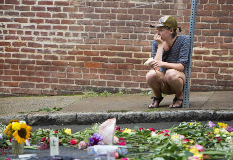 """Charlottesville, VA - August 15:  A woman leaves a flower at 4th and Water Streets Tuesday, August 15 in Charlottesville, Va. where Heather Heyer was killed and 19 others were injured when a car intentionally ran through a crowd of counter protestors after the """"Unite the Right"""" rally Saturday. (Photo by Julia Rendleman for The Associated Press)"""