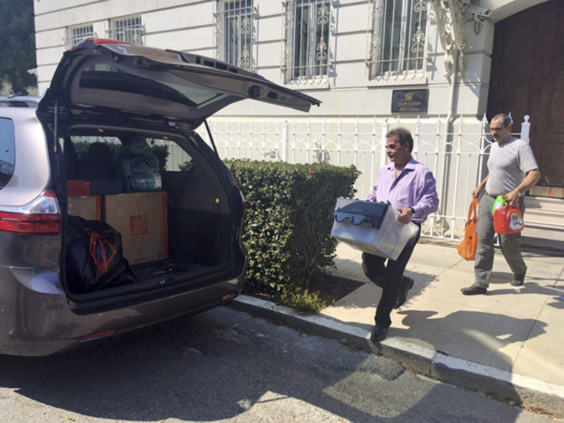 Workers carry boxes out of the Russian consulate in San Francisco as acrid, black smoke was seen pouring from a chimney at the stately building in a historic area of the city Friday, Sept. 1, 2017, a day after the Trump administration ordered its closure amid escalating tensions between the United States and Russia. The workers were hurrying to shut Russia's oldest consulate in the U.S. ahead of a Saturday deadline. (AP Photo/Garance Burke)
