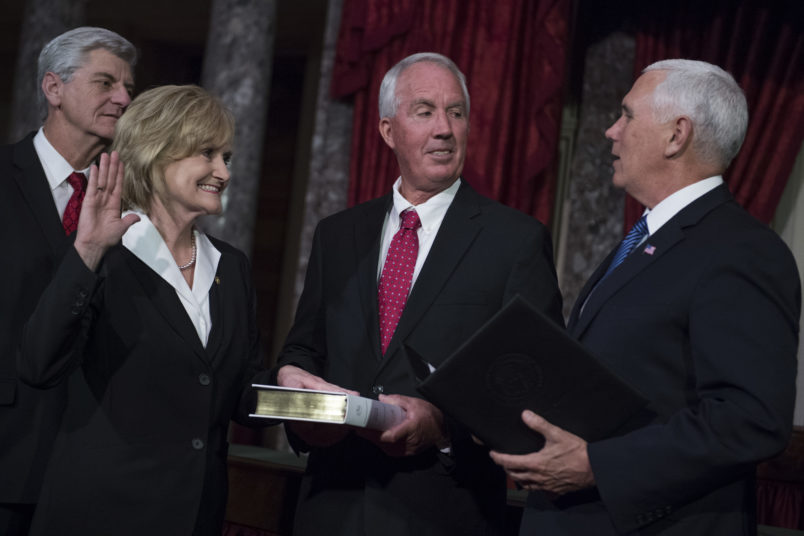 UNITED STATES - APRIL 9: Sen. Cindy Hyde-Smith, R-Miss., participates in her swearing-in ceremony the Capitol's Old Senate Chamber with Vice President Mike Pence, right, and her husband Michael, after being sworn in on the Senate floor on April 9, 2018. Mississippi Gov. Phil Bryant appears at left. (Photo By Tom Williams/CQ Roll Call)