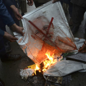 "Pakistani protesters burn a poster of Indian Prime Minister Narendra Modi during an anti-Indian rally in Peshawar, Pakistan, Tuesday, Feb. 26, 2019. Pakistan said India launched an airstrike on its territory early Tuesday that caused no casualties, while India said it targeted a terrorist training camp in a pre-emptive strike that killed a ""very large number"" of militants. (AP Photo/Muhammad Sajjad)"