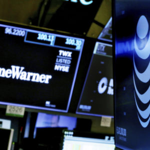 The logos for Time Warner and AT&T appear above alternate trading posts on the floor of the New York Stock Exchange, Wednesday, June 13, 2018. A federal judge has approved the $85 billion mega-merger of AT&T and Time Warner, potentially ushering in a wave of media consolidation while shaping how much consumers pay for streaming TV and movies. (AP Photo/Richard Drew)