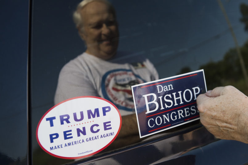UNITED STATES - AUGUST 10: David Peglau puts a bump sticker on his car supporting Dan Bishop, Republican candidate for North Carolina's 9th District, outside of Robin's On Main diner in Hope Mills, N.C., on Friday, August 10, 2019. (Photo By Tom Williams/CQ Roll Call)