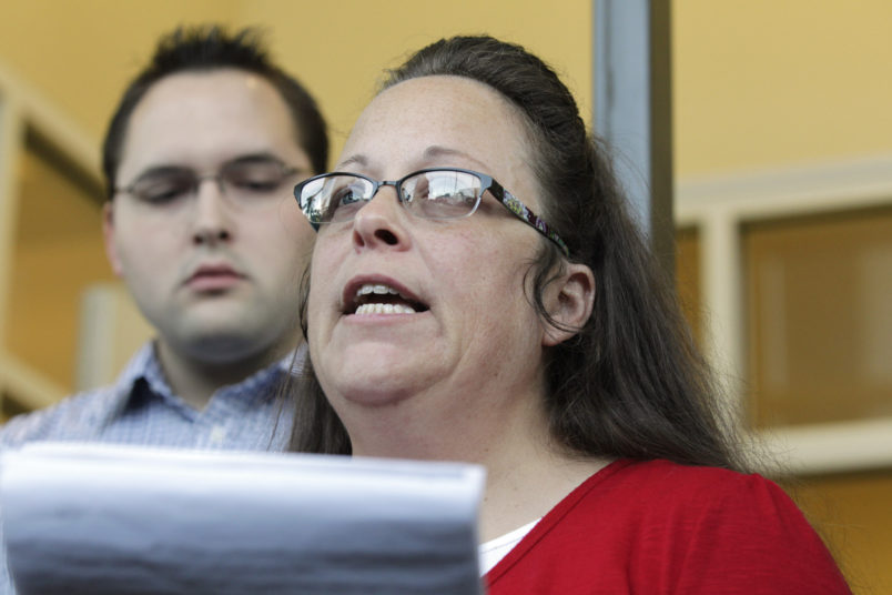 Rowan County Clerk Kim Davis, with son Nathan Davis, a deputy clerk, reads a statement to the press outside the Rowan County Courthouse on Sept. 14, 2015 in Morehead, Ky. Davis did not interfere with marriage licenses issued after she returned to work. (Pablo Alcala/Lexington Herald-Leader/TNS)