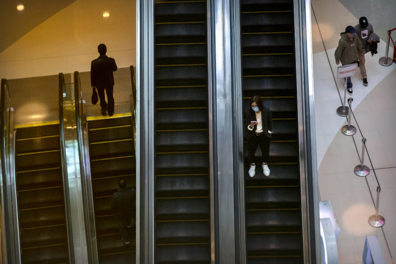 A woman wears a face mask to protect against the spread of the new coronavirus as she rides an escalator at a shopping mall in Beijing, Wednesday, April 15, 2020. China reported several dozen new coronavirus cases on Wednesday, mostly from overseas. (AP Photo/Mark Schiefelbein)