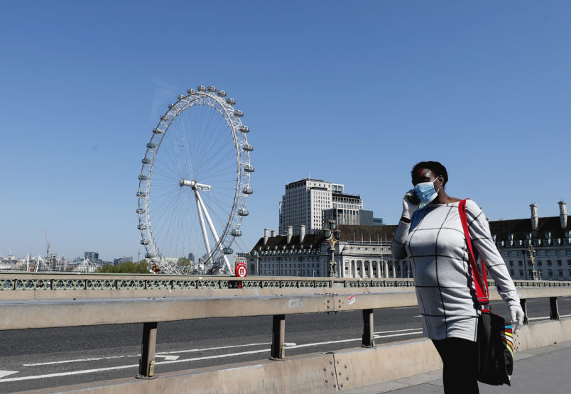 A woman wearing a protection mask walks over Westminster Bridge in London, Wednesday April 22, 2020 during the COVID-19 lockdown. (AP Photo/Frank Augstein)