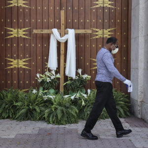 An unidentified man passes the closed front doors of St. Mary's Cathedral as houses of worship closed their doors, but telecast their Sunday Easter services via social media, as large social and religious gatherings are prohibited due to shelter-in-place mandates by local and state governments on Easter Sunday, April 12, 2020 in Miami, Fla. (Carl Juste/Miami Herald/TNS)