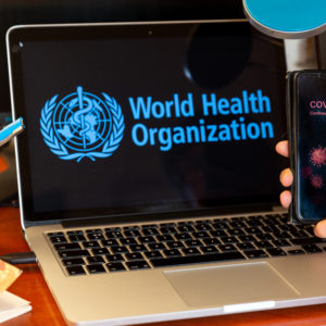 For illustrative purposes a woman holds her mobile phone with a Covid-19 note in front of a computer screen with World Health Organisation logo during Coronavirus pandemic on April 21, 2020. The role of WHO is crucial during epidemics and pandemics. (Photo by Dominika Zarzycka/NurPhoto)