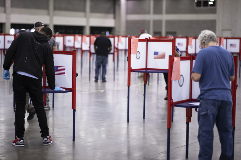 LOUISVILLE, KY - JUNE 23:  A polling worker (left) cleans a voting booth between voters during Tuesday's primary election on June 23, 2020 in Louisville, Kentucky. The Kentucky Exposition Center is the only polling location for Tuesday's Kentucky primary in Jefferson County, home to Louisville and 767,000 residents.  (Photo by Brett Carlsen/Getty Images)
