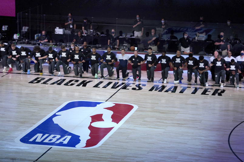 Members of the Milwaukee Bucks and the Boston Celtics kneel around a Black Lives Matter logo before the start of an NBA basketball game Friday, July 31, 2020, in Lake Buena Vista, Fla. (AP Photo/Ashley Landis, Pool)
