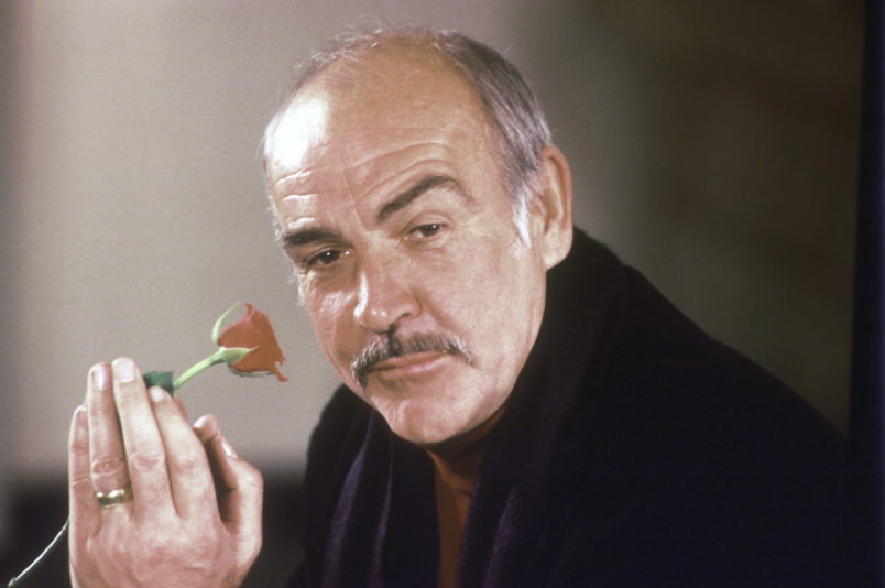 """Actor Sean Connery holds a rose in his hand as he talks about his new movie """"The Name of the Rose"""" at a news conference in London, England, Jan. 23, 1987.  (AP Photo/Gerald Penny)"""