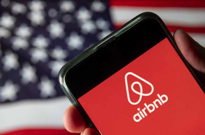 CHINA - 2020/08/15: In this photo illustration the American online marketplace and hospitality service Airbnb logo is seen on an Android mobile device with United States of America flag in the background. (Photo Illustration by Budrul Chukrut/SOPA Images/LightRocket via Getty Images)